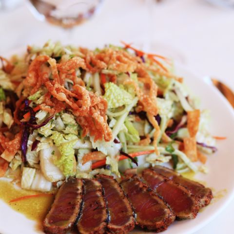 salad with crispy onion straws on top and side meat