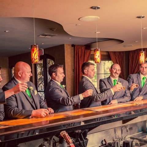 Groomsmen raising a shot glass to toast at the bar