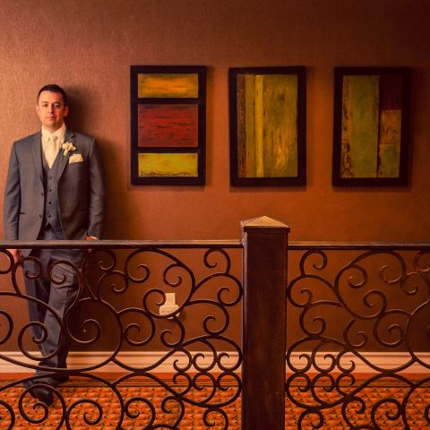 Groom leaning against wall in hotel