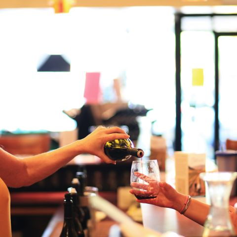 Woman pouring glass of red wine to customer