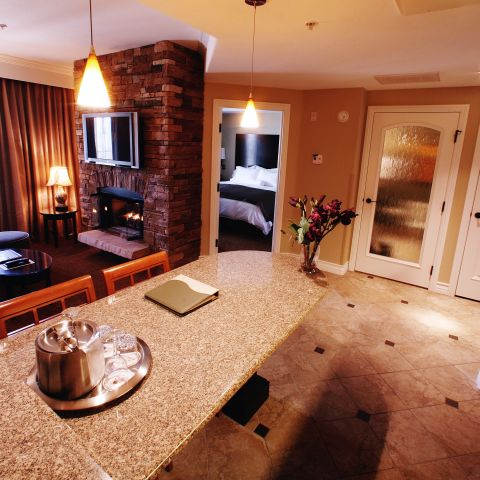 Hotel room wet bar and television over fireplace
