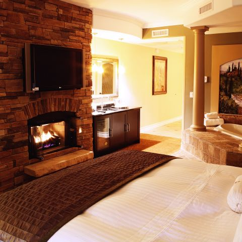 Suite king bed with whirlpool tub and lit fireplace