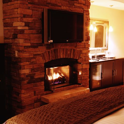 Lit fireplace in room below television, next to sink